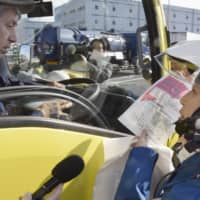 A police officer distributes a leaflet to remind drivers that tailgating is against the law at a parking area of the Metropolitan Expressway in Tokyo. | KYODO