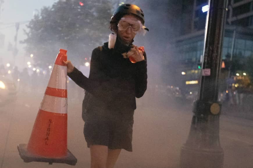 A demonstrator flees a police line after gas was dispensed during a protest in Atlanta on Tuesday.   AP