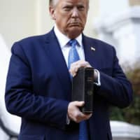 U.S. President Donald Trump holds a Bible as he stands outside St. John's Church near the White House on Monday.  | AP
