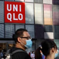 People walk past a Uniqlo store in Beijing on May 24. | REUTERS
