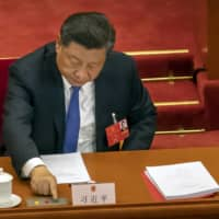 Chinese President Xi Jinping votes on national security legislation concerning Hong Kong during the closing session of China's National People's Congress in Beijing on Thursday. | AP