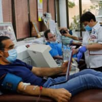 Recovered Israeli COVID-19 patients donate blood samples for plasma extraction Monday, contributing to Israel's new experimental antibodies treatment in Sheba Medical Center Hospital near Tel Aviv. | AFP-JIJI