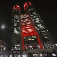The Tokyo Metropolitan Government Building is illuminated in red late Tuesday night, in the first use of the Tokyo Alert warning system after a spike in COVID-19 infections in the capital city. | KYODO