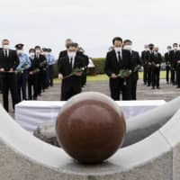 Ryuzaburo Furukawa (center left), mayor of Shimabara, Nagasaki Prefecture, and others lay flowers at a memorial service held at the foot of Mount Unzen on Wednesday, the 29th anniversary of a massive pyroclastic flow that killed 43 people. | KYODO