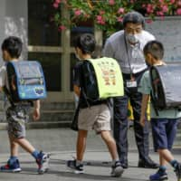 Children are greeted by their principal at an elementary school in the city of Nara on Monday. | KYODO