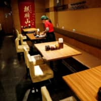 A waitress cleans a table at a restaurant in Tokyo on May 8 as businesses struggled under coronavirus measures. | REUTERS