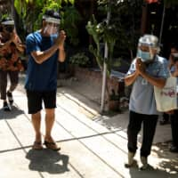 Surin Makradee leaves a house in Ang Thong province, Thailand. Makradee and other volunteers nationwide check people's temperatures and gather data to prevent the spread of the coronavirus.  | REUTERS