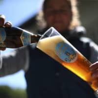 A woman pours a beer outside her family's 120-year-old brewery in Altoetting, Germany, last month.  | AP