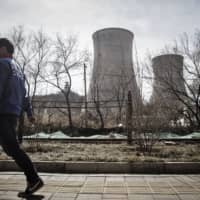 A man walks past cooling towers at the Beijing Jingneng Power Co. Thermal Power Plant in Beijing in 2016. | BLOOMBERG