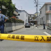 A police office stands guard near the house where two women were killed by arrows in Takarazuka, Hyogo Prefecture, on Thursday. | KYODO