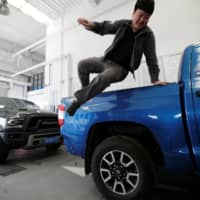 A worker jumps off a Toyota Tundra pickup truck at Pickup Fan Club, on the outskirts of Beijing. | REUTERS