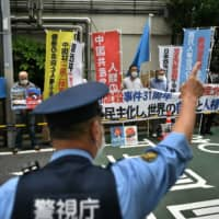 A police officer directs traffic as pro-democracy activists hold a silent prayer before a protest at the Chinese Embassy in Tokyo on Thursday, the 31st anniversary of the June 4, 1989, crackdown on democracy protests in Beijing. |  AFP-JIJI
