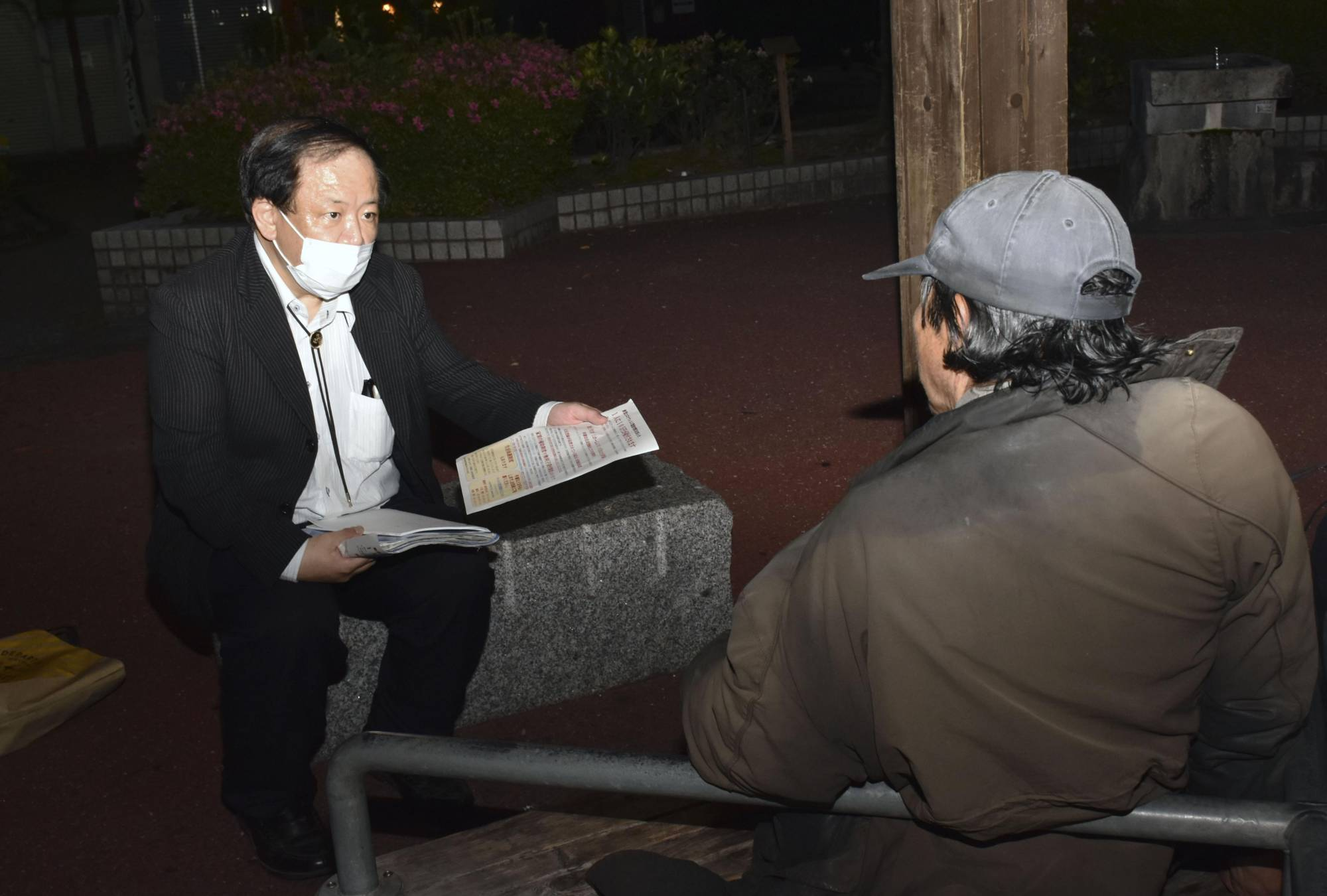 Kiyomu Tanaka, a professor at the University of Kochi versed in community-based welfare, hands a flyer to a homeless person that explains the government's cash handout program in the city of Kochi on May 11. | KYODO