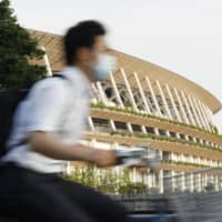 A man rides past the National Stadium in Tokyo, the main venue of the delayed Olympics and Paralympics, on Thursday. | KYODO