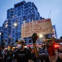 Protesters break curfew and march in the Chelsea neighborhood of New York City on Thursday. Protests have continued following the death of George Floyd, who died after being restrained by Minneapolis police officers on May 25.   | AP