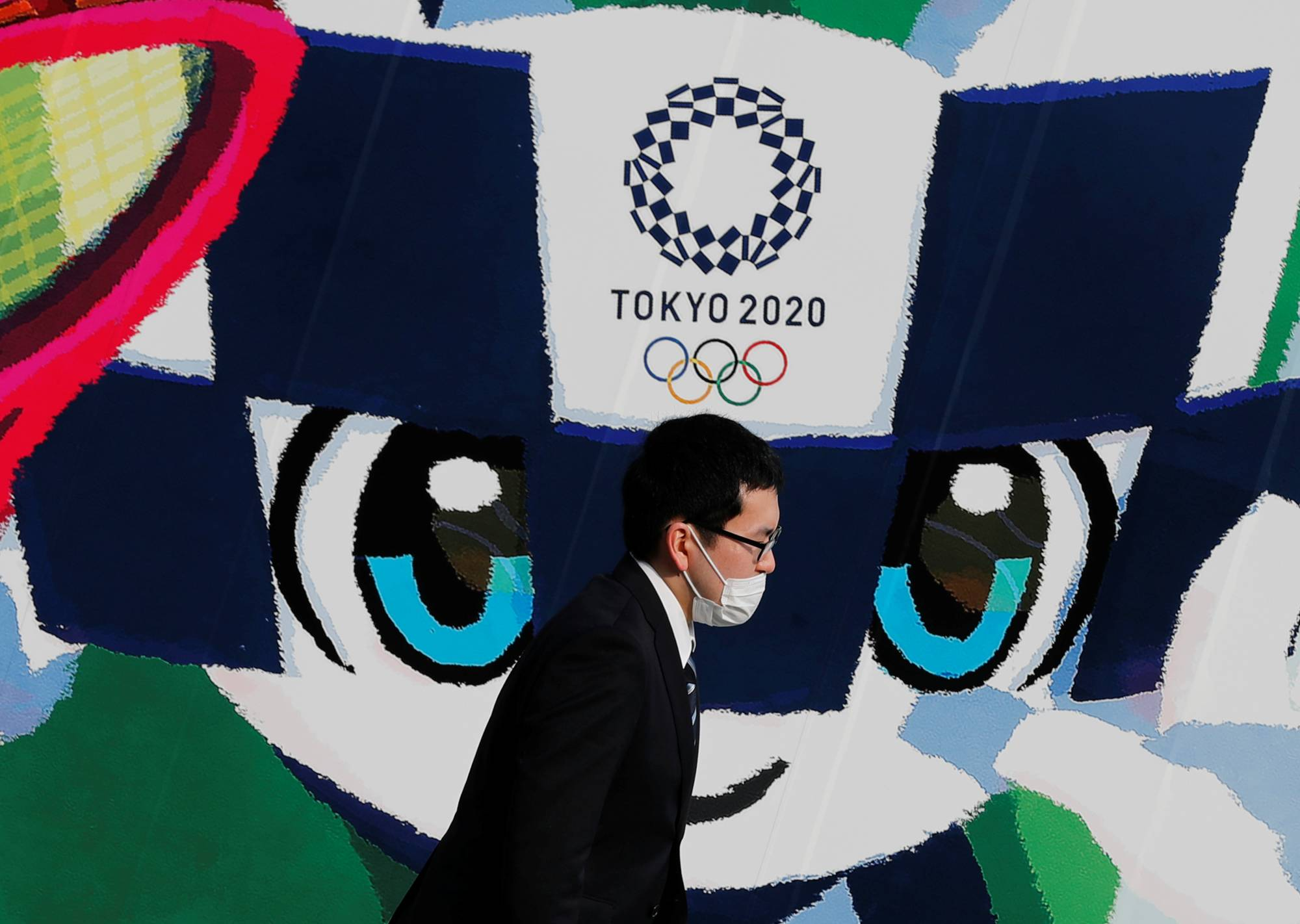 A man walks past a poster promoting the 2020 Tokyo Olympics on Thursday in Tokyo.   REUTERS