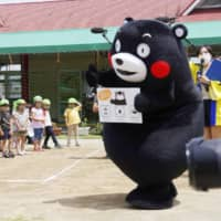 Kumamon calls on children to wash their hands during a surprise visit to a nursery school in Kosa, Kumamoto Prefecture, on Friday. | KYODO