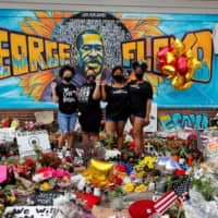 Protesters have gathered and left flowers at the site where George Floyd died in Minneapolis, Minnesota, on May 25. | REUTERS