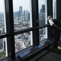 A man wearing a protective mask looks outside from the observation deck of Tokyo Tower.  | AP