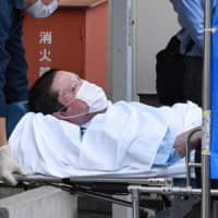 Suspect Shinji Aoba is brought into Fushimi Police Station on a stretcher in Kyoto on May 27. | KYODO