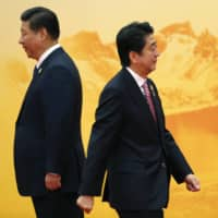 Prime Minister Shinzo Abe walks past Chinese leader Xi Jinping during a welcoming ceremony of the Asia Pacific Economic Cooperation forum, inside the International Convention Center at Yanqi Lake, Beijing, in November 2014. | REUTERS