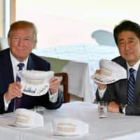 U.S. President Donald Trump Prime Minister Shinzo Abe pose after they signed and exchanged hats reading 'Donald and Shinzo, Make Alliance Even Greater' at the Kasumigaseki Country Club in Kawagoe, Saitama Prefecture, in November 2017. | POOL / VIA REUTERS