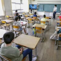 Students sit at safe distances from one another at an elementary school in the city of Nara on June 1. | KYODO