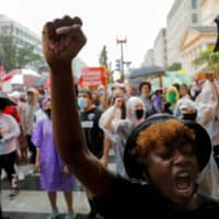 A demonstrator raises her fist as she takes part in a protest over the death in Minneapolis police custody of George Floyd, in Washington on Friday. | REUTERS