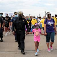 Detroit Police Commander F.D. Hayes walks with his daughter, Joslyn, and wife, Rochelle Doran-Hayes, in a peace march across the MacArthur Bridge to rally against the death in Minneapolis police custody of George Floyd, in Detroit on Friday. | REUTERS