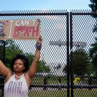 A woman holds a placard as she takes part in a protest over the death in Minneapolis police custody of George Floyd, in Washington, on Friday. | REUTERS