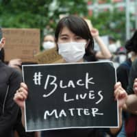 A woman holds a sign during the Black Lives Matter protest Saturday in Tokyo. | RYUSEI TAKAHASHI