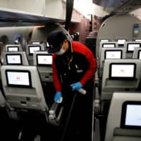 A staff member of Japan Airlines cleans the cabin of a plane for a domestic flight, amid the coronavirus outbreak at Haneda airport in Tokyo on May 26, 2020. Picture taken May 26.   REUTERS