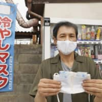 Katsuyuki Goto, a managing director at knit maker Knit Y'Z in Yamanobe, Yamagata Prefecture, holds a mask made by his company last month that incorporates an ice pack.  | KYODO