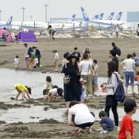 People play at a seaside park in Tokyo on Saturday near the Haneda airport. | KYODO