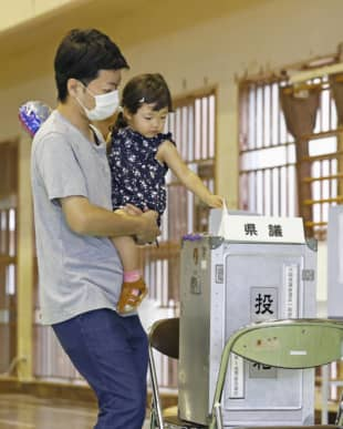 A voter casts a ballot at a polling station in Naha in the Okinawa Prefectural Assembly election on Sunday. | KYODO