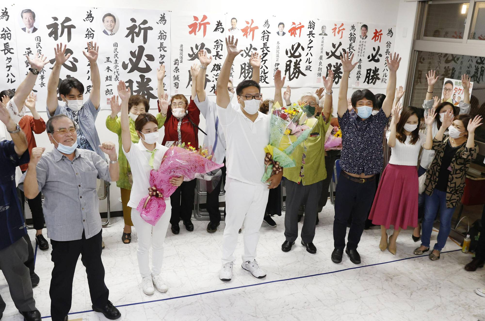 An Okinawa prefectural assembly election candidate (center) supporting Okinawa Gov. Denny Tamaki applauds with supporters Sunday in Naha, Okinawa Prefecture, after winning a seat. | KYODO