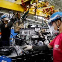 Employees wearing protective face masks and face guards work on an automobile assembly line in Kawasaki. Japan's economy shrank less than initially estimated, revised data showed Monday. | REUTERS