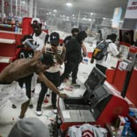 Looters raid a Target store on Minneapolis' Lake Street, a major commercial thoroughfare that is home to dozens of black-owned businesses, during riots that followed the May 25 death of George Floyd. | STAR TRIBUNE / VIA AP