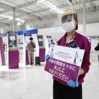 A Peach Aviation Ltd. employee asks passengers to practice social distancing at Kansai Airport in Osaka Prefecture on Friday. | KYODO