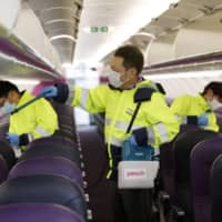 Workers disinfect the interior of a Peach Aviation airplane at Kansai Airport in Osaka Prefecture on Friday. | KYODO