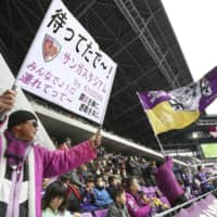 A fan (right) waves a flag resembling a Nazi death's head flag during a preseason game between Sanga and Cerezo on Feb. 9 at Sanga Stadium in Kameoka, Kyoto Prefecture. The J. League fined Sanga ¥1 million for the flag on Monday. | KYODO