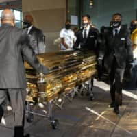 George Floyd's casket is brought out of Fountain of Praise church following a public visitation on Monday in Houston. | HOUSTON CHRONICLE / VIA AP