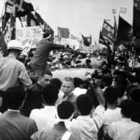 Labor union members surround White House Press Secretary James C. Hagerty's car at Haneda Airport on June 10, 1960. | KYODO