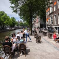 Customer sit socially distanced in a section of road on an expanded cafe terrace area beside the Herengracht Canal  in Amsterdam on June 1. | BLOOMBERG
