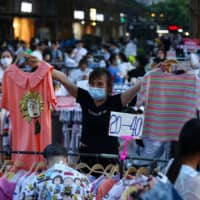 A street vendor sells clothes at an outdoor market in Wuhan on Monday.  | STR / VIA AFP-JIJI