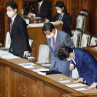 (From right) Prime Minister Shinzo Abe, Finance Minister Taro Aso and economic revitalization minister Yasutoshi Nishimura bow Wednesday after a draft second supplementary budget was approved during a Lower House plenary session. | KYODO