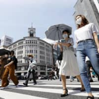 People walk under a strong sun in Tokyo's Ginza shopping area on Tuesday, wearing face masks amid continued worries about the novel coronavirus. | KYODO