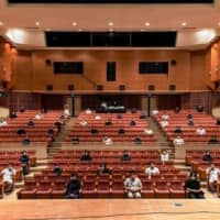 A composite photo posted on Facebook on May 8 shows what it would look like if people practiced social distancing at the 398-seat Ginoza Village Cultural Center Garaman Hall in Okinawa Prefecture. | THE OKINAWA TIMES
