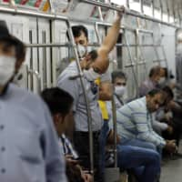 Iranians, mostly wearing face masks, are pictured in a train carriage at a metro station in the capital Tehran on Wednesday.    | AFP-JIJI