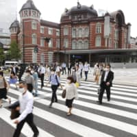 Commuters head to work near Tokyo Station on May 25. | KYODO